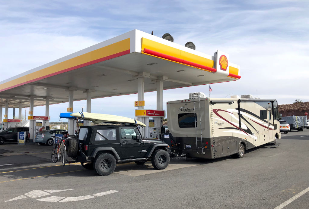 an RV towing a Jeep Wrangler fueling up at a shell station