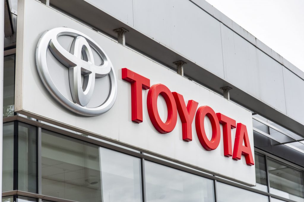 a silver Toyota logo with the red TOYOTA letters on the side of a dealership building