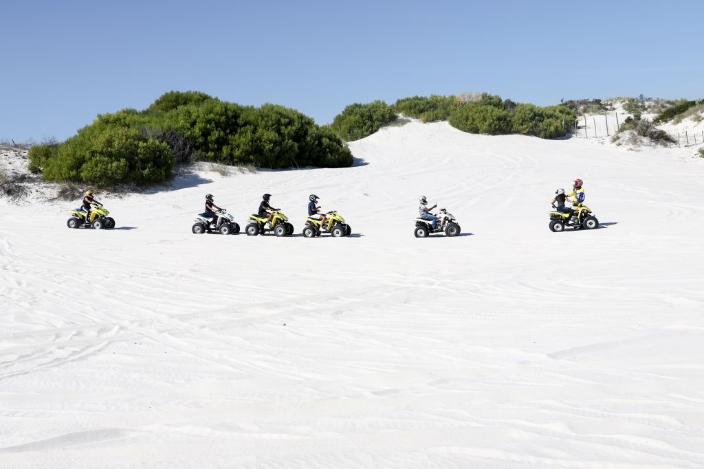 several ATV riders traversing scenic sand dunes