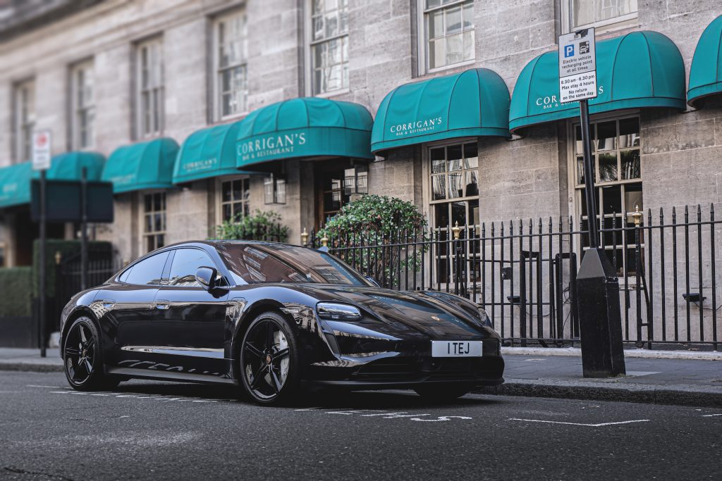 An image of a Black Porsche Taycan parked outdoors in one of the worst car colors for resale.