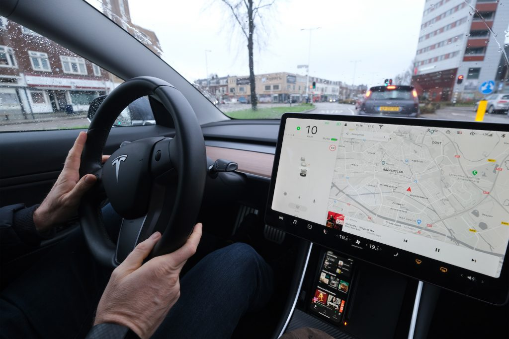 An image of a person steering a Tesla through a city.