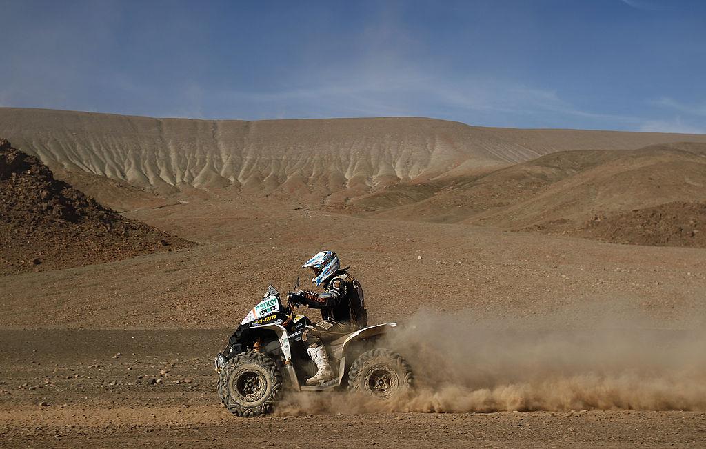 an ATV rider on a Can-Am at the Dakar Rally riding through a vast desert