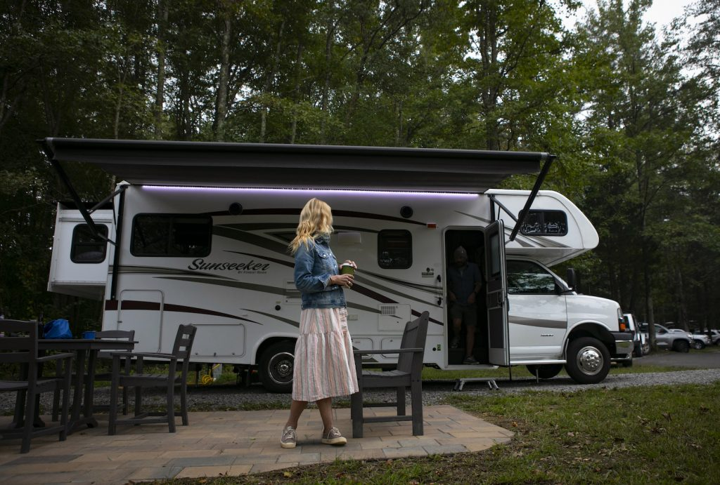 A woman in a pink dress stands in front of an RV at an RV campground.