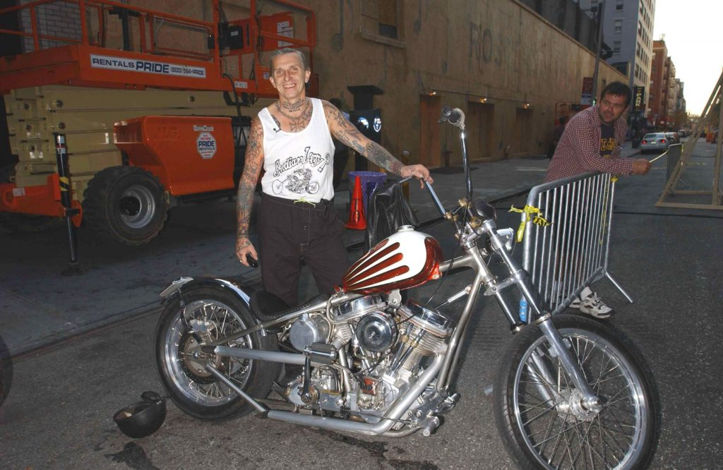 Indian Larry on the street outside of The Late Show with Dave Letterman Show with one of his custom red-and-white-painted choppers