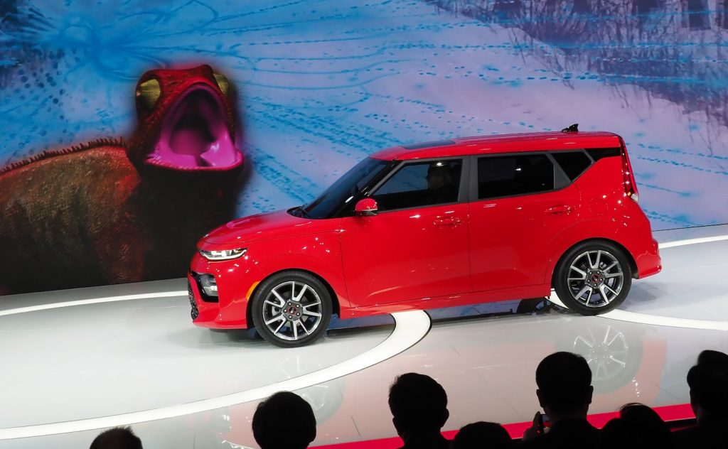 A red Kia Soul GT being unveiled at an auto show.