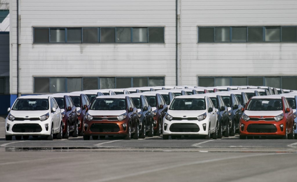 Kia cars sit in a row on awaiting export
