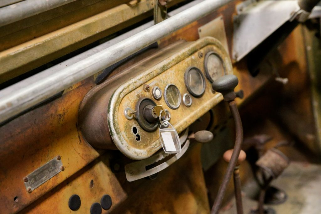 A closeup of a Land Rover Series One's ignition switch and starter button with its key