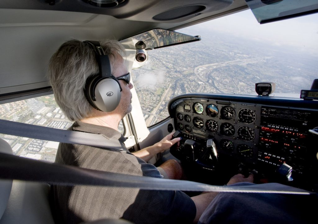 A man flying a Cessna plane over California