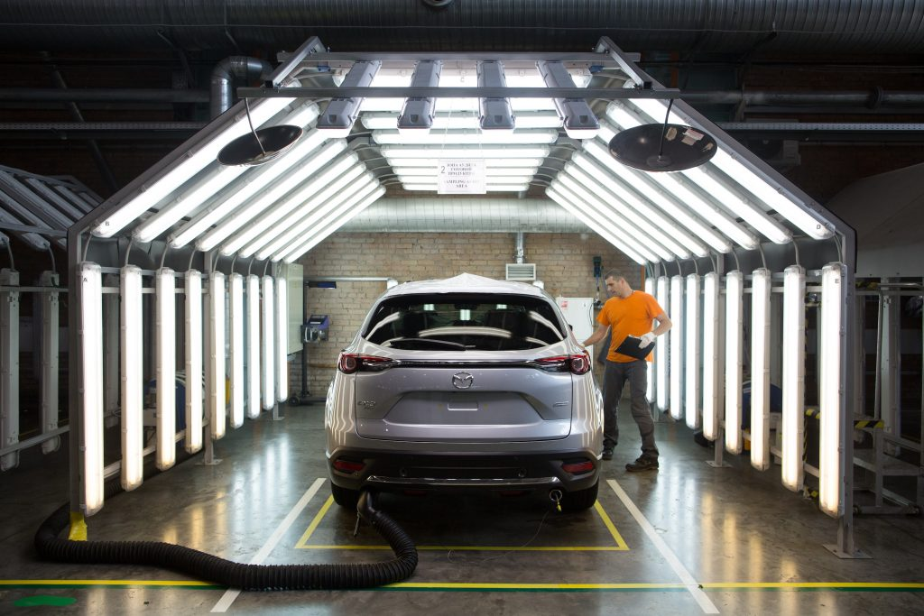 A worker inspects a Mazda Motor Corp. CX-9 sports utility vehicle (SUV) in a light tunnel at the Mazda Sollers Manufacturing Rus LLC plant