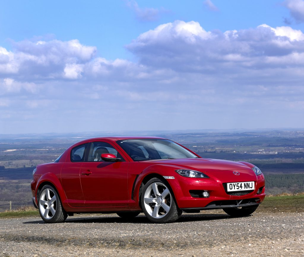 Red Mazda RX8 coupe JDM car parked on a hill