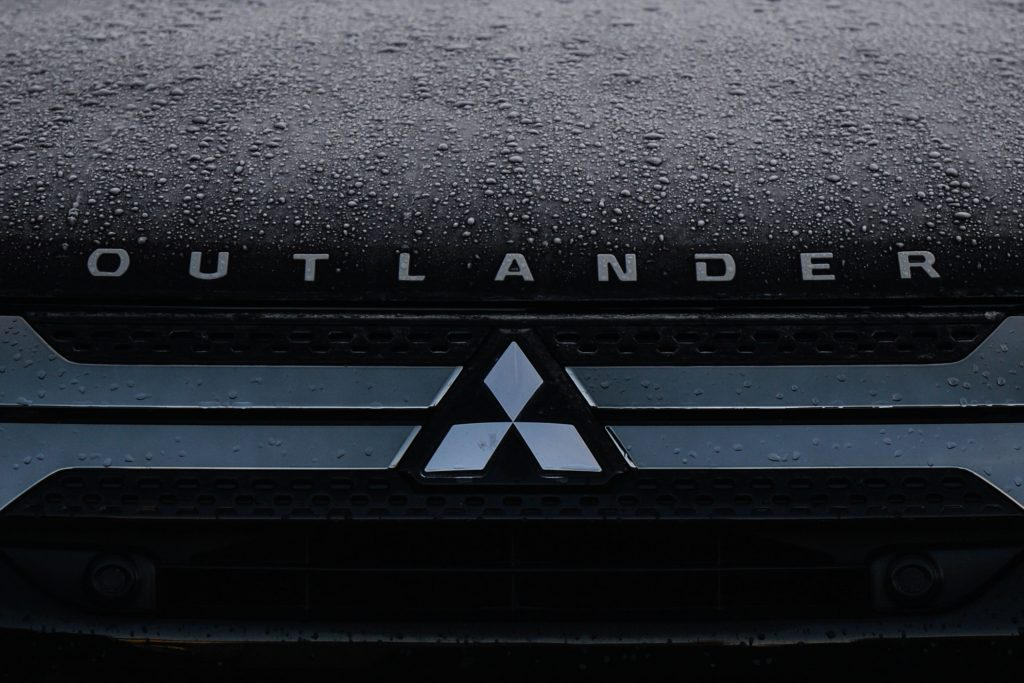 A Mitsubishi logo seen on a parked 2022 Mitsubishi Outlander car in Dublin city center.