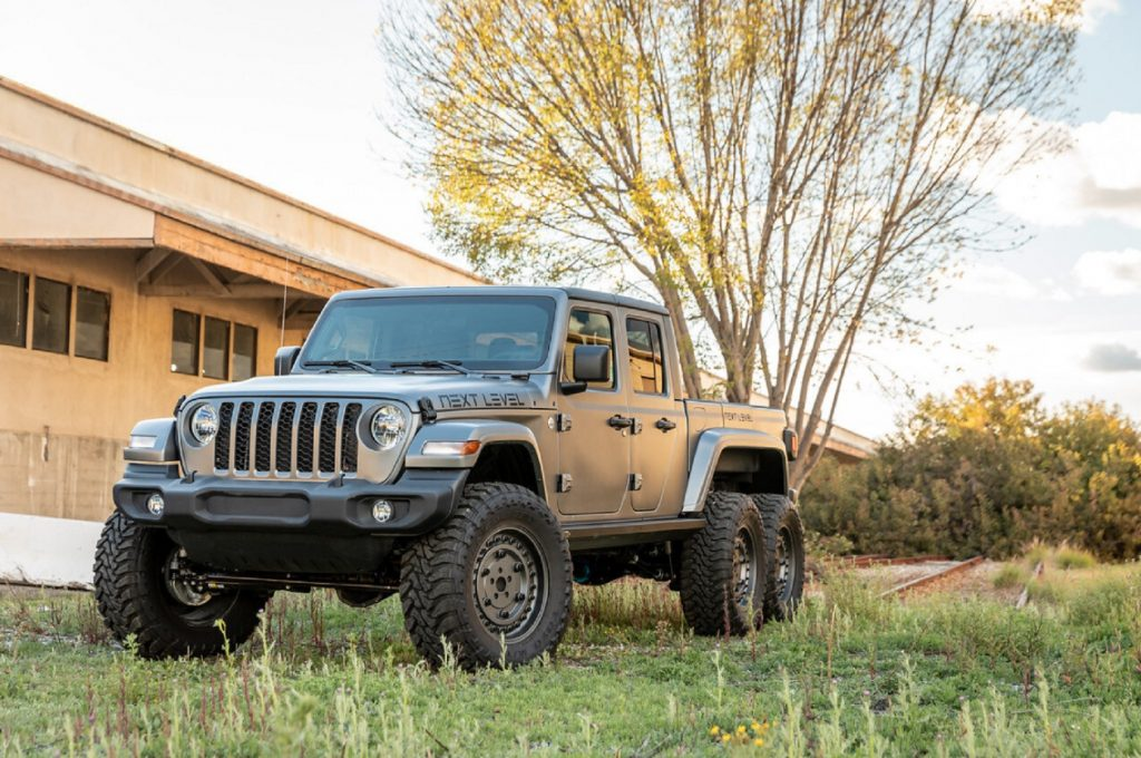 A matte-gray Next Level Jeep Gladiator 6x6 parked by a yellow-stone building's lawn