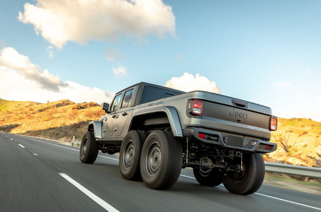 A low-angle rear 3/4 view of a matte-gray Next Level Jeep Gladiator 6x6 driving on a hilly road