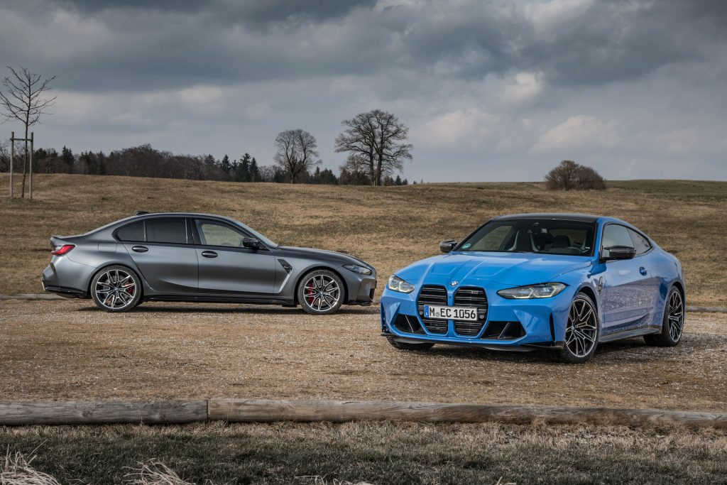 An image of a BMW M3 and M4 xDrive parked outside.