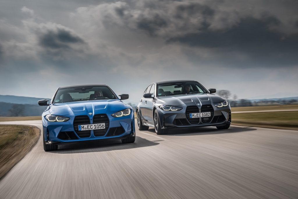 An image of a BMW M3 and M4 xDrive driving on a road.