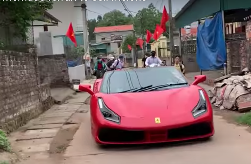 Phony Ferrari driving down narrow Vietnamese street