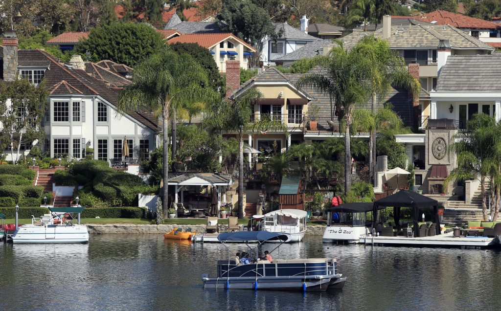 An electric-powered pontoon boat skims across Lake Mission Viejo, past the homes and private docks