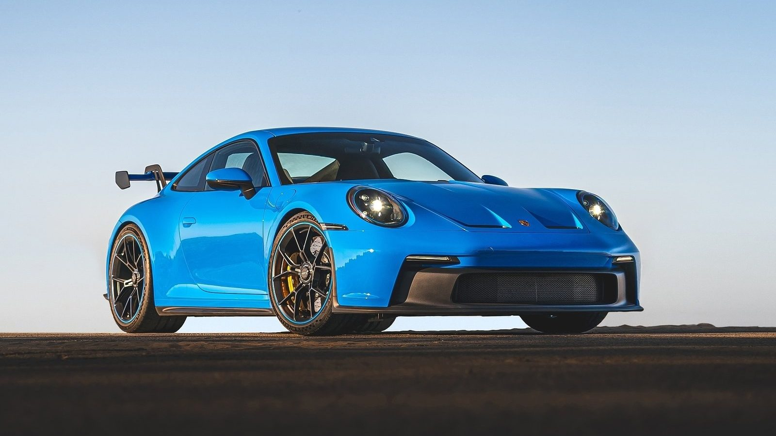 An image of a blue 2022 Porsche 911 GT3 on a track.