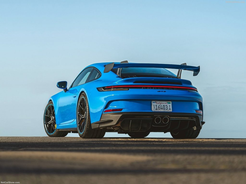 The rear view of a blue 2022 Porsche 911 GT3 on a track.