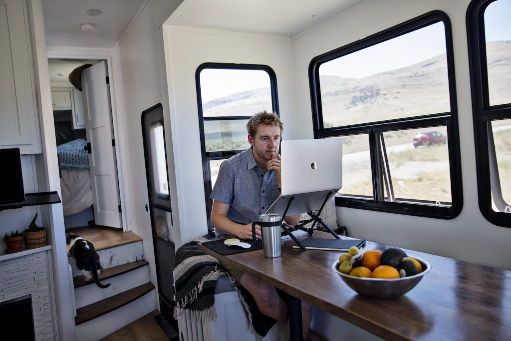 A man sitting inside of his RV, accessing RV WiFi via his computer.