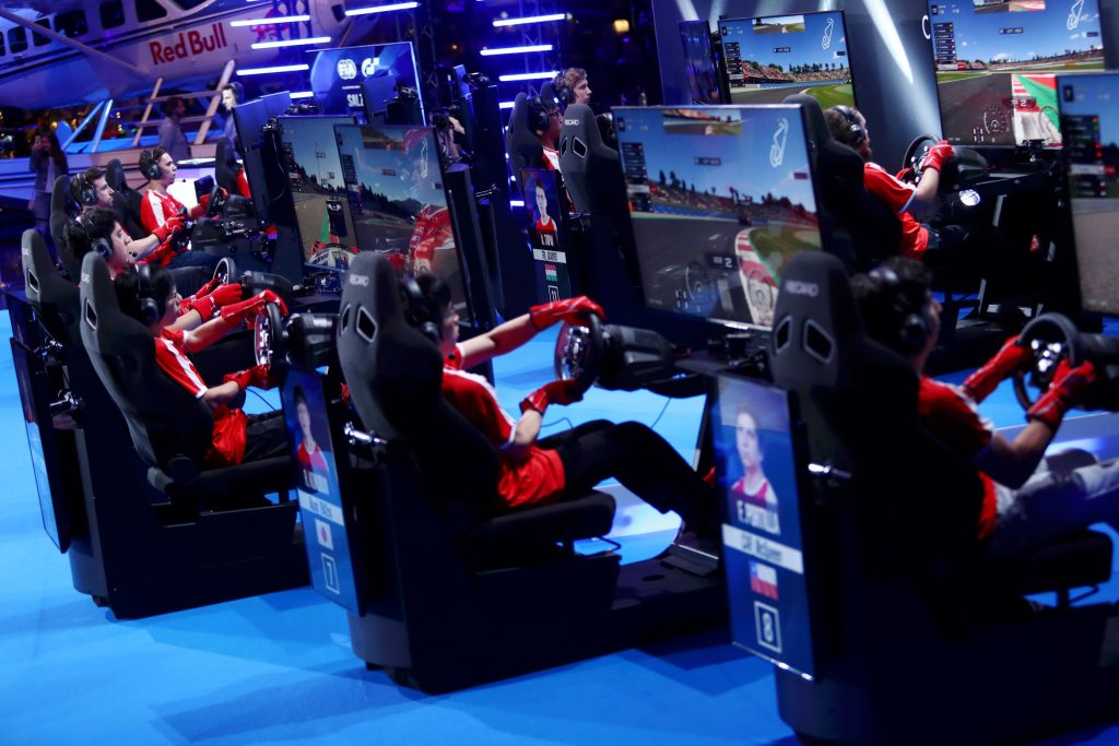 Red-clad racers competing on simulators in the 2019 FIA Gran Turismo World Tour Nations Cup in Salzburg