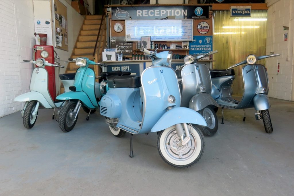 Several Retrospective Scooters Project E electric vintage Vespa scooters in a garage