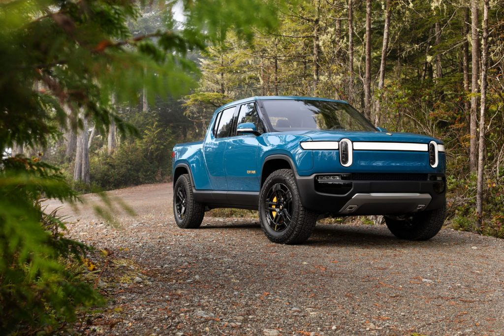 A blue Rivian R1T parked on a gravel road in a forest