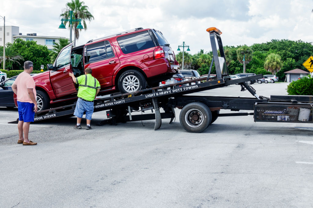 A red SUV being loaded onto the back of a flatbed tow truck