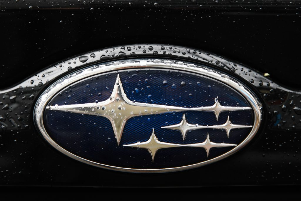 The Subaru Logo with flecks of water on it.