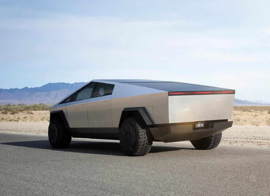 The rear 3/4 view of the stainless-steel Tesla Cybertruck concept on a desert track