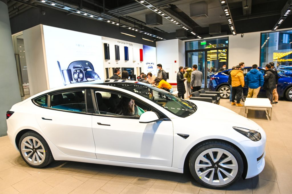 A white Tesla Model 3 vehicle is seen at a Tesla flagship store