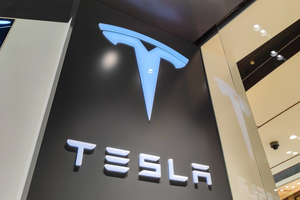 A Tesla sign lit up at a store