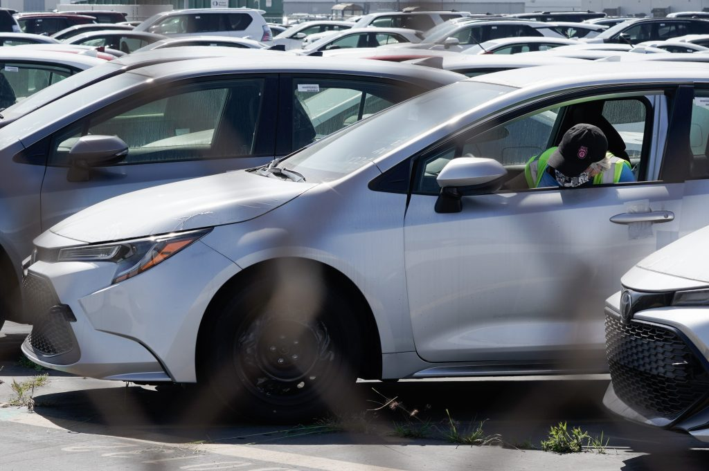 A worker parks a silver Toyota Motor Corp. Corolla vehicle at a Toyota Logistics Services Inc. automotive processing terminal at the Port of Los Angeles