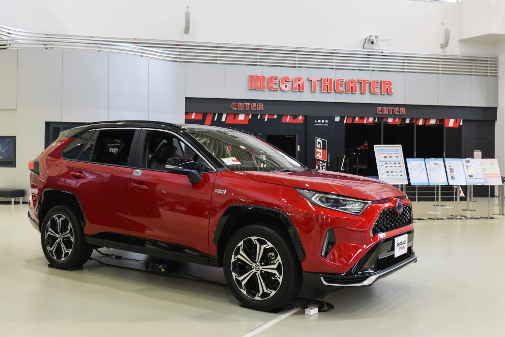 A red Toyota Motor Corp. RAV4 plug-in hybrid sports utility vehicle (SUV) stands on display at the Toyota Mega Web showroom in Tokyo, Japan