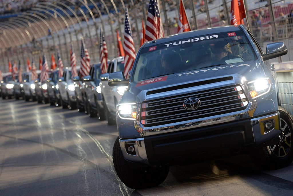 A lineup of Toyota Tundra pickup trucks driving a few miles around a track.