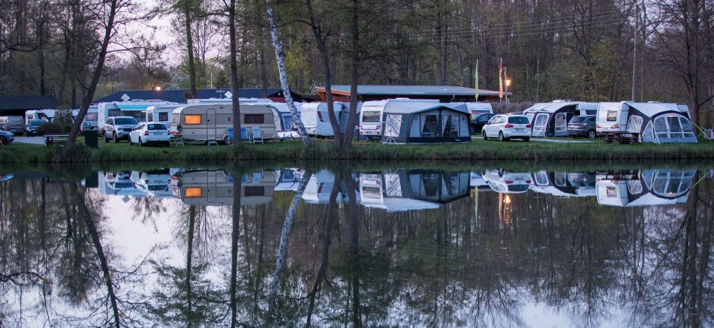 Travel trailers and other RVs at a camping site overlooking a lake