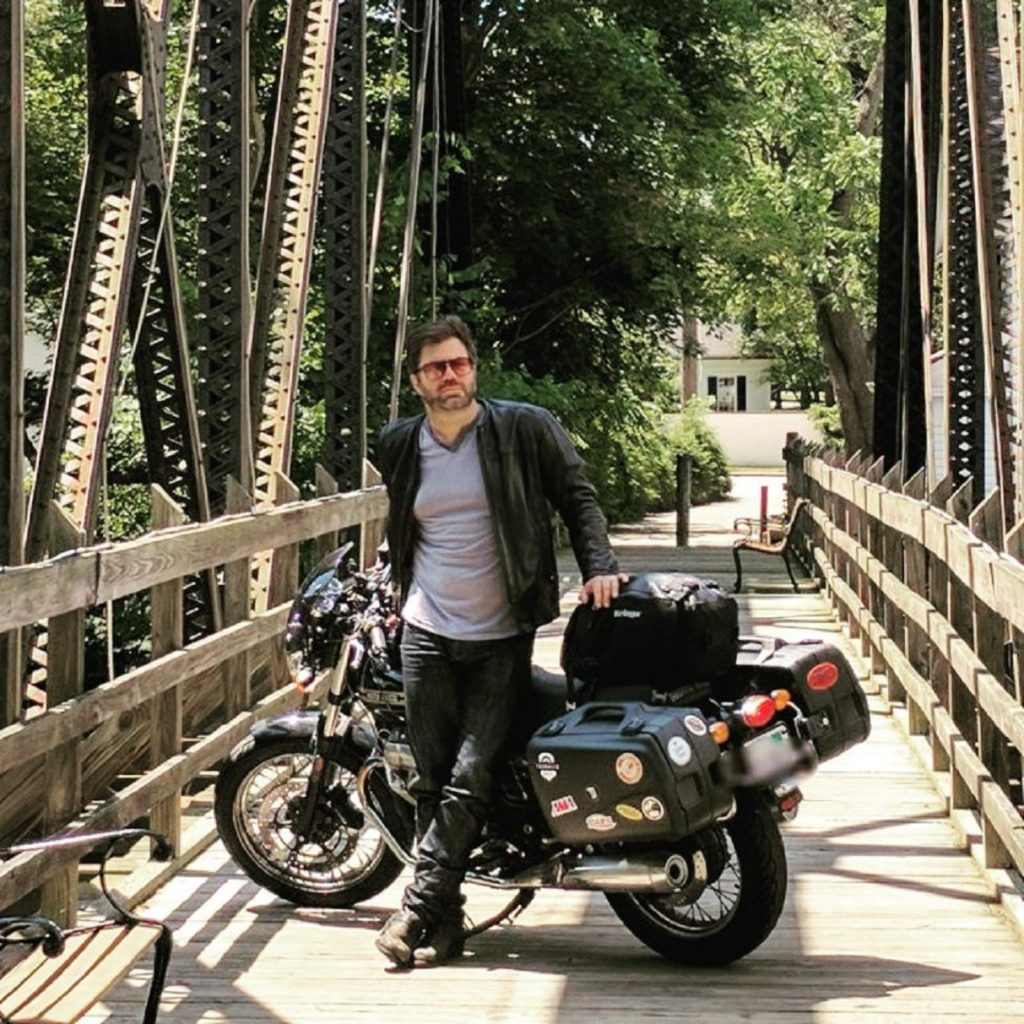 Twisted Road founder Austin Rothbard with his black-and-gold 2010 Moto Guzzi V7 Classic on a bridge