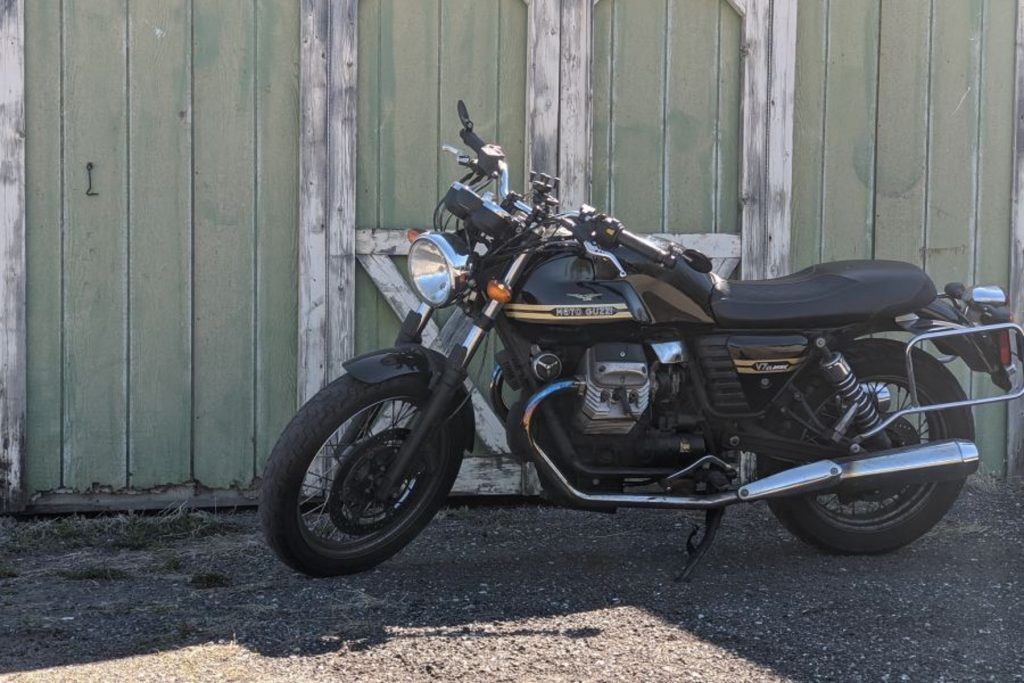 Twisted Road founder Austin Rothbard's black-and-gold 2010 Moto Guzzi V7 Classic next to a green warehouse