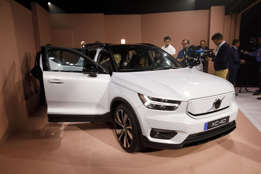 Members of the media view the white Volvo XC40 Recharge electric sports utility vehicle (SUV) during an unveiling event in Los Angeles, California, U.S.