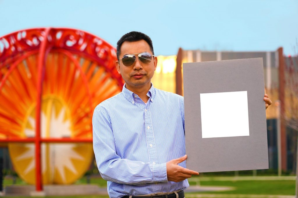 Xiulin Ruan standing with a sample of the whitest white paint
