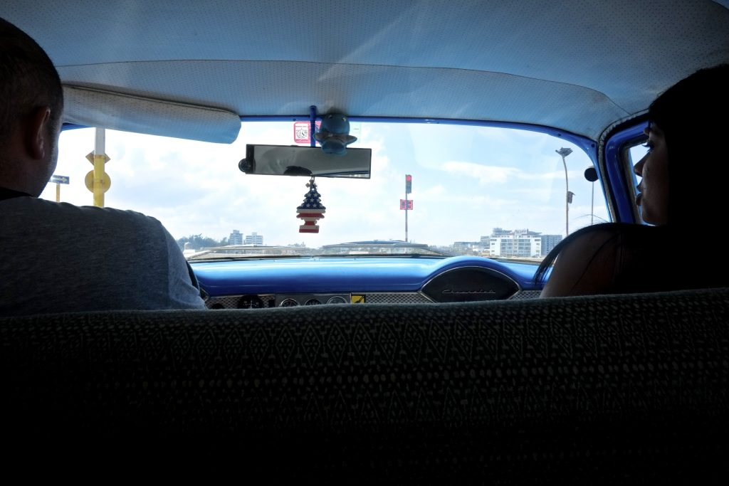 An American flag air freshener hangs from the rearview mirror of a cab.