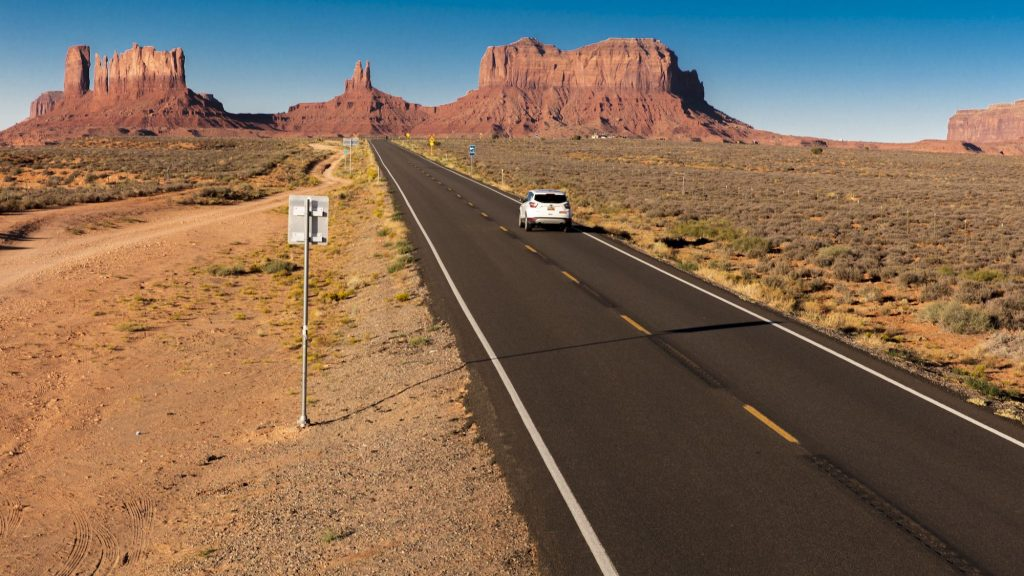 A white SUV on a road trip drives toward Monument Valley on the Utah-Arizona border in the American Southwest
