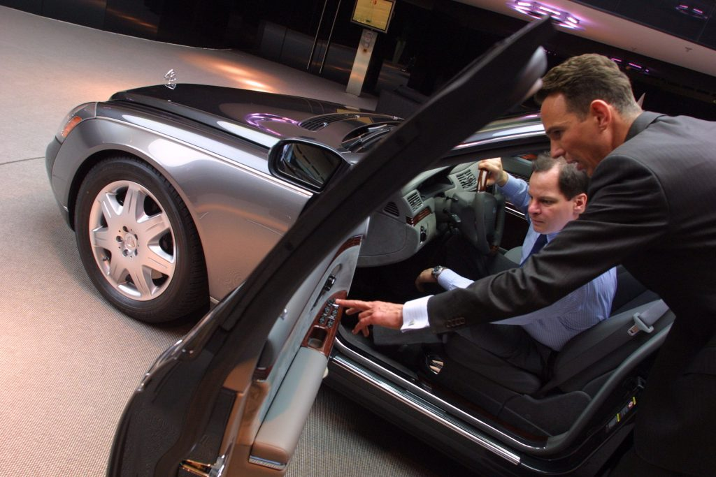 A salesman shows a potential customer detail on a Maybach 57 limousine.