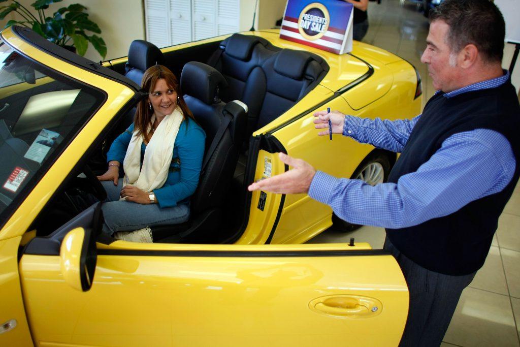 A car salesman shows a new Saab to a customer at the Deel Saab dealership