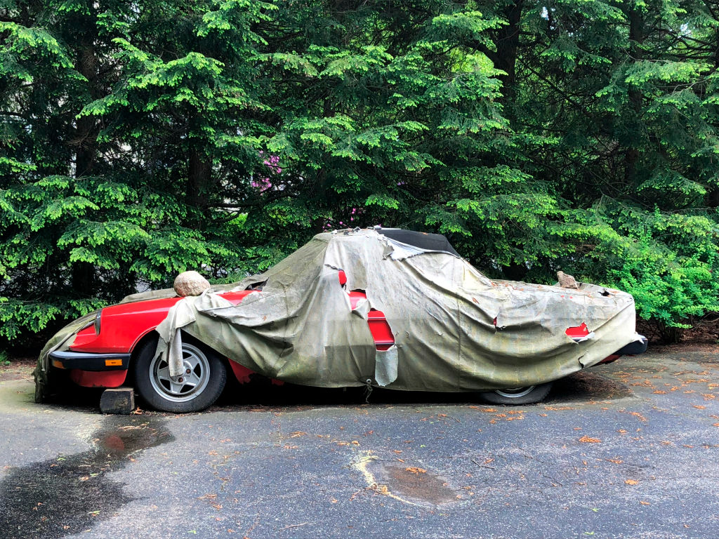 A rusted red classic Ferrari underneath an old ripped protective covering