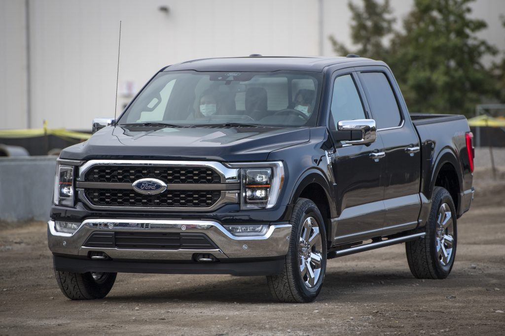 The front end of the ford f150 pickup truck on the road