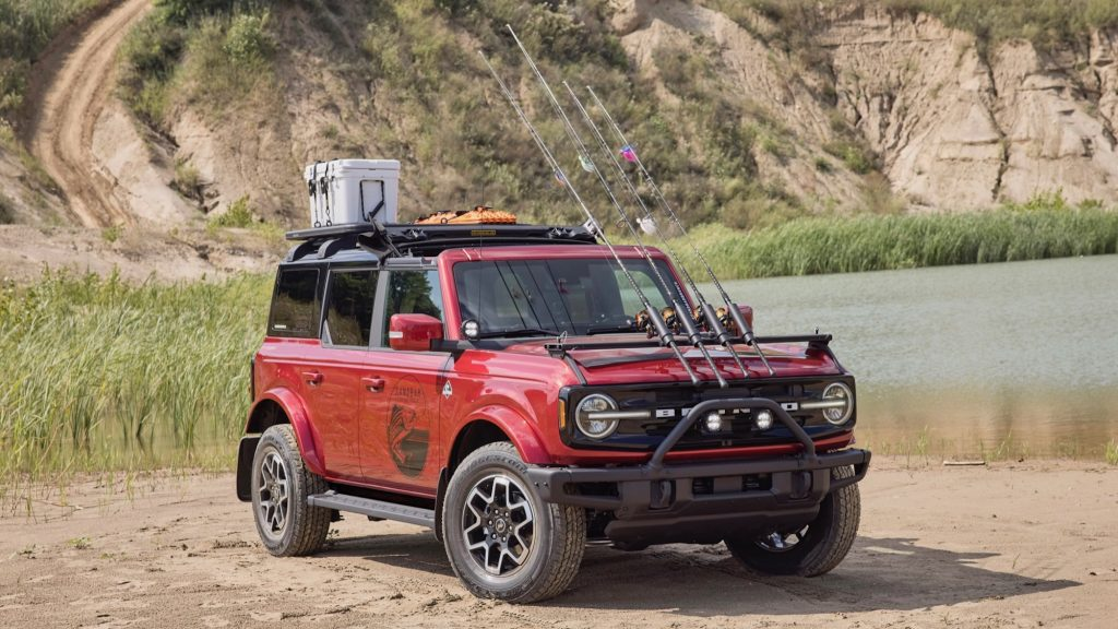 2021 Ford Bronco in red covered in fishing gear pared next to a pond