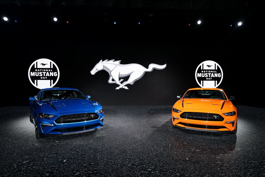 A blue Ford Mustang and orange Ford Mustang on display with a contrasting black backdrop