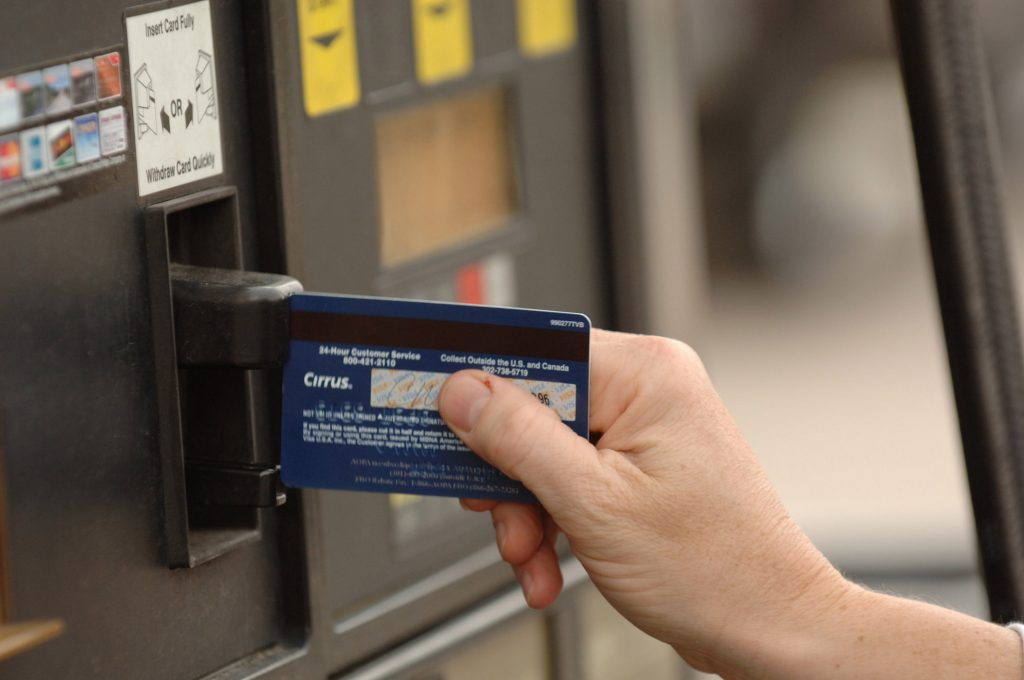 A customer swipes her credit card at a gas pump in a Conoco gas station.