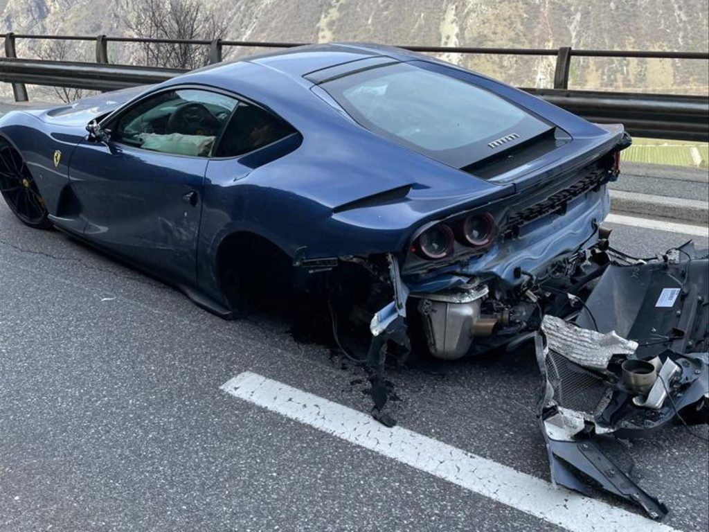 An image of a crashed Ferrari 812 Superfast on the side of the road.